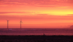 © Licensed to London News Pictures. <br /> 09/12/2014. <br /> <br /> Teesside, United Kingdom<br /> <br /> A man walks along the beach as a beautiful sunrise starts the day over Teesside. Strong winds are expected to pick up through the day as the winter weather continues.<br /> <br /> <br /> Photo credit : Ian Forsyth/LNP
