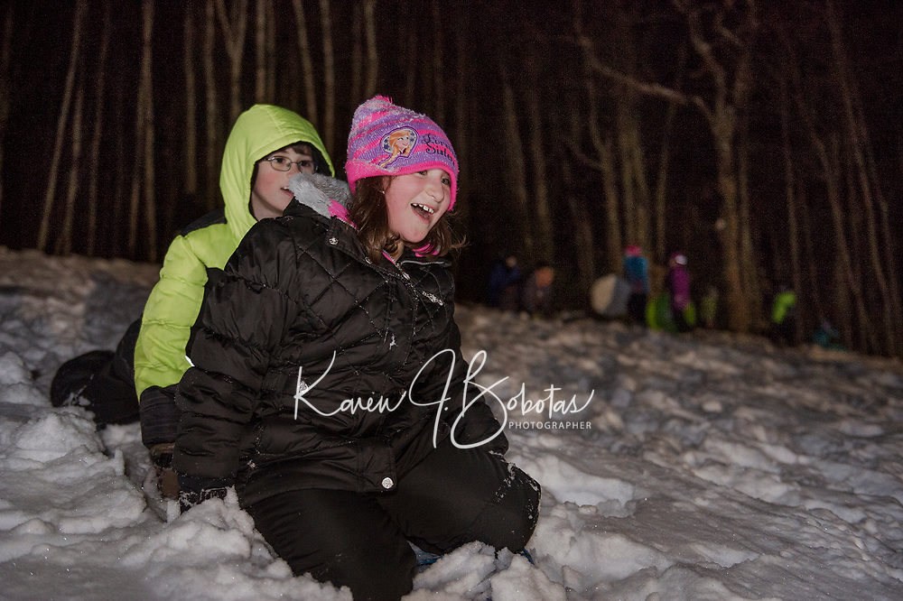 Chloe and Corbin take a ride down the sledding hill at Memorial Hill during Laconia Parks and Rec's Sledding Party on Friday evening.  (Karen Bobotas/for the Laconia Daily Sun)