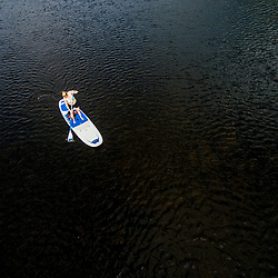 A woman paddleboarding on Second Roach Pond near the Appalachian Mountain Club's Medawisla Lodge in the Maine Woods near Greenville.
