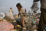 Child recycling workers collecting plastic bags on Smokey Mountain rubbish dump. The bags are sold by the kilo, at about 10 cents of a dollar. Plastcis, wirtes and even hospital waste, syringes for instance sell for 1 centime a piece are recycled., Many children and families work doing this work...RUBBISH DUMP RECYCLING. South East Asia, Cambodia, Phnom Penh. Smokey Mountain, Steung Mean Chey, is Phnom Penh's municipal rubbish dump. Thousands work there, some 600 minors and 2000 adults, recycling the city's rubbish, dumped there by garbage trucks every day. The dump is notorious as many very young children work there. People eat and sleep overnight in the rubbish and fumes, under plastic tarpaulins or in the open air. They work 24 hours a day, like miners, with headlamps at night, collecting plastic, metals, wood, cloth & paper, which they sort and clean, weigh and sell, to be carried away for recycling. A day's work typically brings less than a dollar per person. One and a half to two dollars per day per family. The overpowering, acrid odour of grey smokey fumes blows across the dump, from which the place gets its name 'Smokey Mountain'. It can be smelt miles away. The shantytowns and squats, the recycling worker's homes butt onto or are inside the dump itself. There is no running water, sanitation and many are ill. Children often work with friends or relatives. Religious and ngo's help some children, but this is often resisted by families who need the extra income they generate.///Using fire to separate metal from plastic and rubber, a recycling worker takes advantage of the permanently burning rubbish.