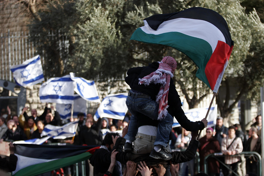 Israeli right-wing students hold Israeli flags (left) and Left-wing Jewish and Arab students hold a Palestinian flag (right) during simultaneous demonstration for and against the military operation on the Gaza Strip, in front of the Hebrew University in Jerusalem, on March 3, 2008.
