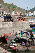 Unloading fish and loading ice in fishing vessels at Cat Ba town fishing port, Cat Ba Island, Vietnam
