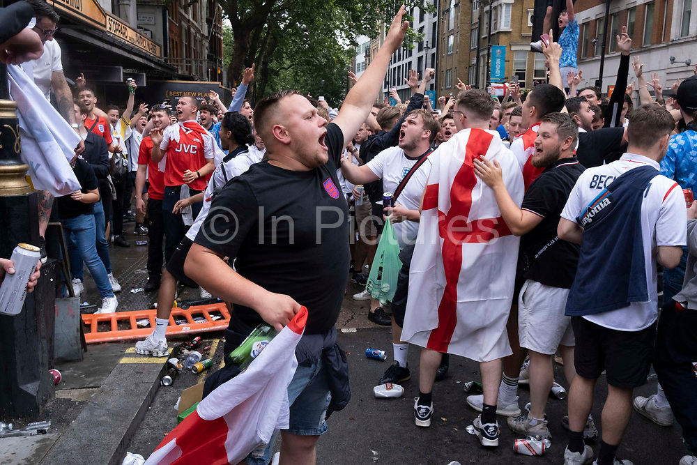 Hours before the England football team play an historic game against Italy the first time since 1966 that the English national team have played in a major mens international football final, thousands of mainly young supporters crowd without face coverings nor social distancing outside Leicester Square tube station, on 11th July 2021, in London, England.