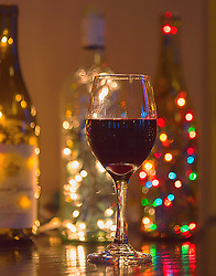 Christmas lights sparkle from behind this moody red wine glass