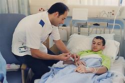 Staff nurse giving young patient intravenous antibiotics,