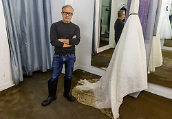 Licensed to London News Pictures. 05/10/2021. London, UK. Fashion designer Jacques Azagury and former dressmaker to Princess Diana surveys one of his £9,000 silk organza Ivory wedding dress ruined by flood water in his shop in Knightsbridge, west London after torrential rain hit large parts of London last night. Heavy rainfall has caused severe flooding in London with roads blocked with flood water and cars trapped. Photo credit: Alex Lentati/LNP