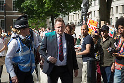@Licensed to London News Pictures 17/06/2017. Central London, UK. A suited member of the public is showered in luminous glitter during the No Coalition of Chaos with the DUP protest outside Downing Street today in Central London.Photo credit: Manu Palomeque/LNP