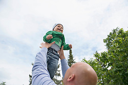 Father holding baby boy in arms playing flying