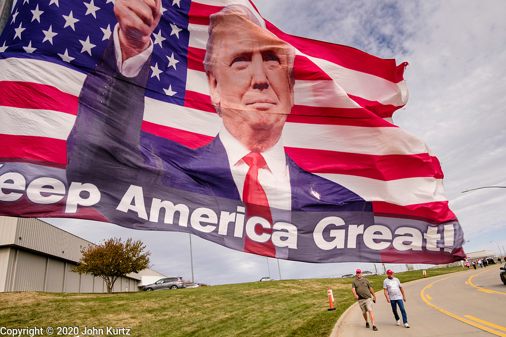 14 OCTOBER 2020 - DES MOINES, IOWA: People walk to a campaign rally for President Donald Trump. About10,000 people were expected at the Des Moines International Airport for a campaign rally supporting the reelection of President Trump. Trump spoke at the rally, despite testing positive for COVID-19 less than three weeks ago. The rally did not meet the CDC guidelines for a safe gathering in the time of Coronavirus and violated Iowa's health emergency declarations barring gatherings of more than 25 people. This week Iowa exceeded 101,000 cases of COVID-19 and a surge in hospitalizations for COVID-19.       PHOTO BY JACK KURTZ