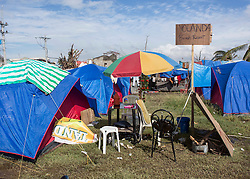 26/11/2013.  A sign makes a joke of one of the many tented sites that are now home to those whose homes were destroyed by a super typhoon in the city of Tacloban in the Philippines.  Photo credit: Alison Baskerville/LNP