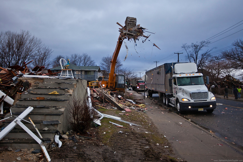 The remnants of a demolished house are loaded into the back of a tractor trailer, Union Beach.
