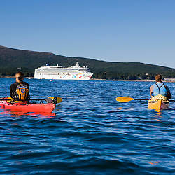 A young couple sea kayaking near the Porcupine Islands in Maine's Acadia National Park.  Frenchman Bay.  Bar Harbor. A cruise ship is in the distance.