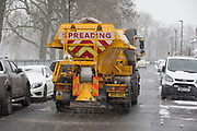 A Lambeth council gritting lorry spreads grit between parked cars on a minor road in the south London borough, on 28th February 2018, in London, England.