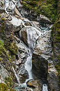 Snowy Creek cascades from Rees Saddle above Dart Hut on the Rees-Dart Track in Mount Aspiring National Park, Otago region, South Island of New Zealand. Glacier-clad Mt Edward rises above.