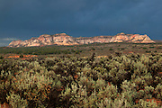 The white and multi-colored Elkheart Cliffs stand out against dark storm clouds over Mt. Carmel Junction, Utah.