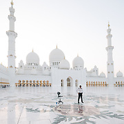 A man stands guard at the famous Sheikh Zayed Grand Mosque at sunset.