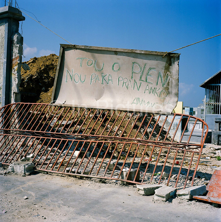 "A sign in front of a mass grave containing hundreds of bodies at the main cemetery in Port Au Prince. The sign reads: ""The hole is full. We have no more room for bodies""."