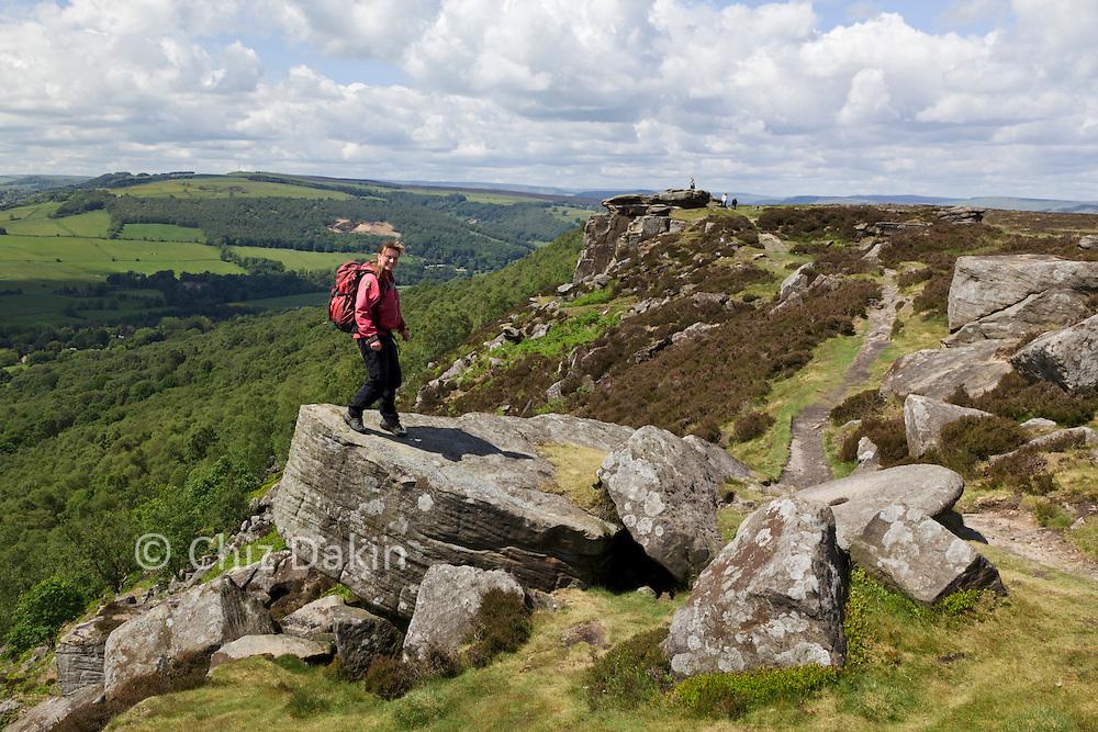 Walker (Chiz Dakin) standing on an airy boulder above Curbar Edge.