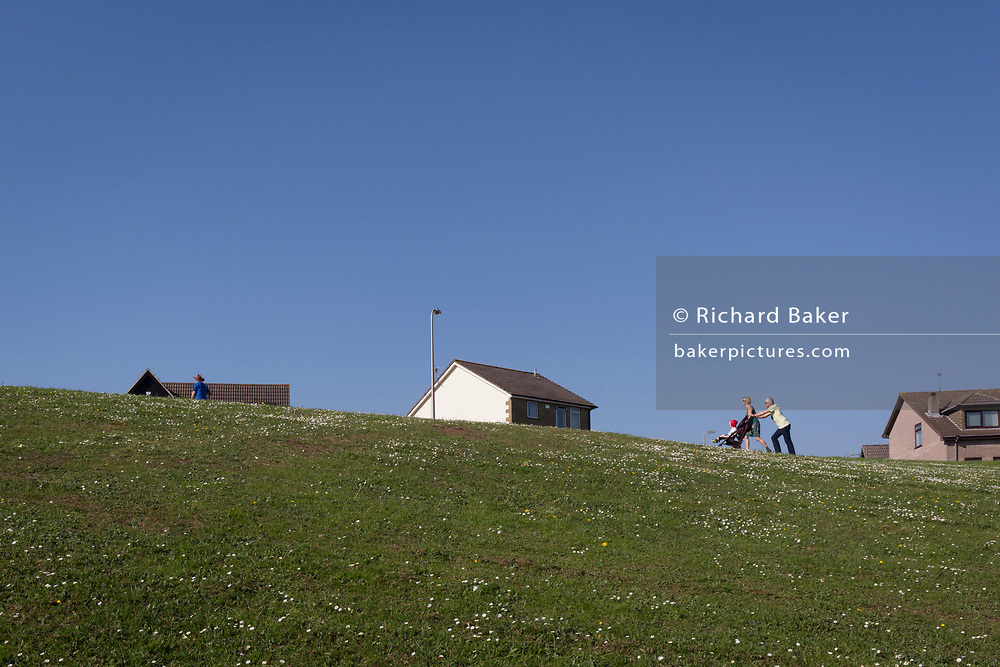 A local family walk uphill towards the houses of a nineteen-eighties, middle-class housing estate on 21st April 2019, in Nailsea, North Somerset, England