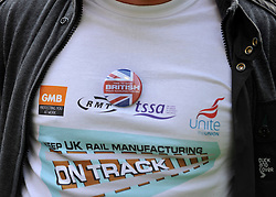 """© licensed to London News Pictures. LONDON, UK.  07/09/11. Detail of a t-shirt worn by a worker from Derby. A large group of Unite members working at Bombardier, along with business leaders and Derby councillors call on the government to """"save British train manufacturing"""" outside parliament today. The delegation's visit, which coincides with the Transport Committee hearing, includes Unite general secretary Len McCluskey, the leader of Derby City Council and the Mayor of Derby.. Mandatory Credit Stephen Simpson/LNP"""