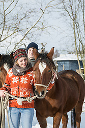 Young couple standing with horses in barn, Bavaria, Germany