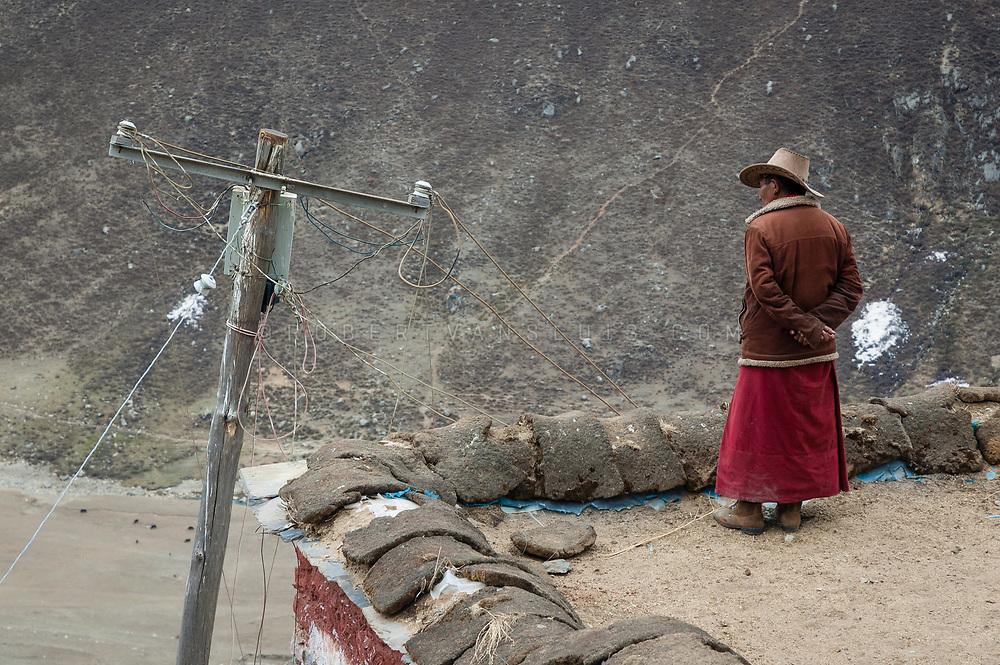 Man on the roof of Drigung Til Monastery, Tibet, China. Photo © robertvansluis.com