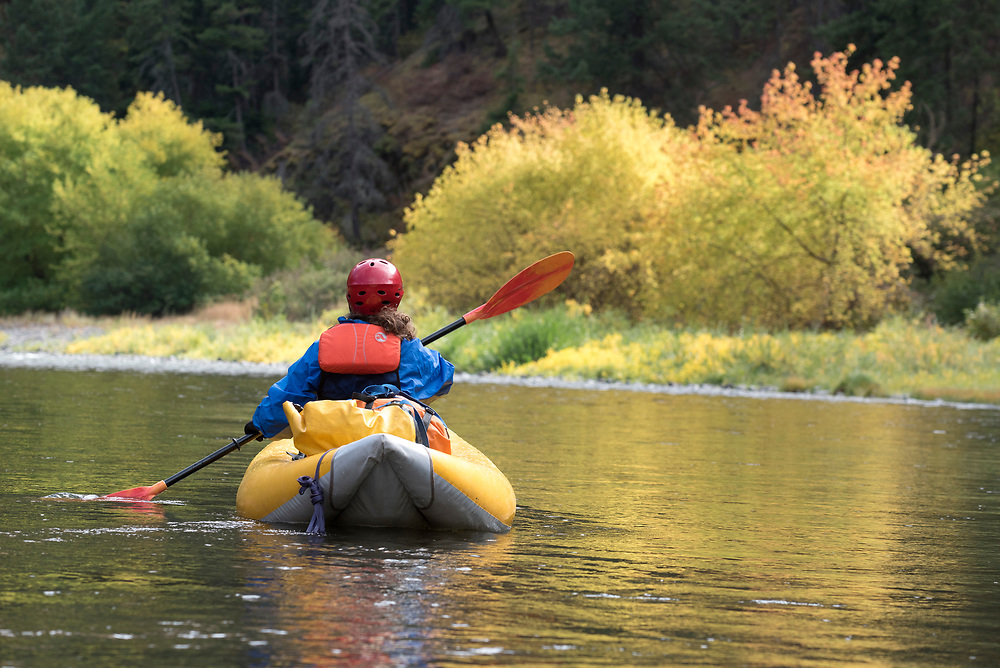 Woman paddling an inflatable kayak down the Grande Ronde River in Northeast Oregon.