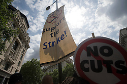 © licensed to London News Pictures.  30/06/2011. London, UK. A climber hangs a banner from a lamp post as public sector workers and Union members demonstrate in London today (30/06/2011) against planned changes to pension plans and funding cuts. Marches are taking place across the UK.  See special instructions. Photo credit: Ben Cawthra/LNP