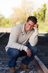 good looking man smiling outdoors by a railroad track
