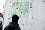 Greece . Chios Island, one of the places where refugees from Turkey land en route to Northern Europe. Souda camp. A refugee looks at a map showing the location of Chios.