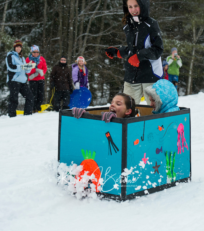 """Avi Bartlett and Olivia Salesky ride inside the """"Coral Reef"""" while teammate Brianna Salanitro runs along side during Gilford Parks and Recreation annual Cardboard Derby race at the Outing Cluyb Wednesday morning.  (Karen Bobotas/for the Laconia Daily Sun)"""
