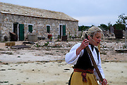 Young woman in traditional Croatian dress, traditional stone building in background. Pakovo Selo--Drnis, Croatia