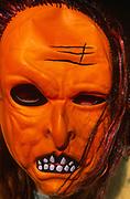 A3ABK3 Child wearing scary orange Halloween mask