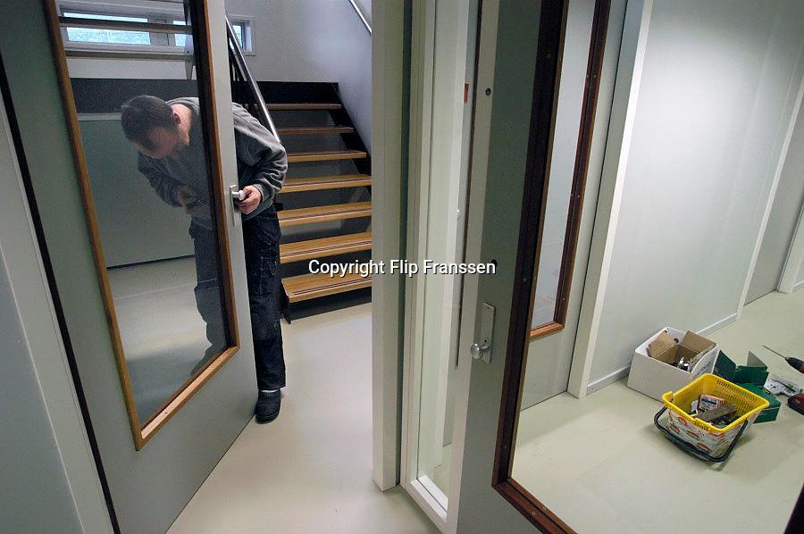Nederland, Arnhem, 3-12-2010Timmerman brengt sloten aan tijdens laatste werkzaamheden uit aan nieuwbouwproject. Slot vervangen.Foto: Flip Franssen/Hollandse Hoogte