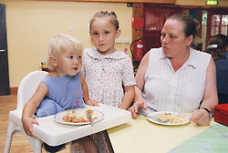 Mother sitting with two young girls eating lunch at surviving homelessness project,