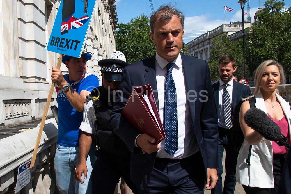 A police officer intervenes as a  pro remain protester heckles Julian Smith MP, Secretary of State for Northern Ireland as he leaves the Cabinet office in Whitehall, London, United Kingdom on 20th August 2019.