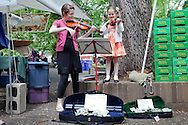 The extremely popular Saturday Portland Farmers' Market, located in the South Park Blocks near the Portland State University Campus, offers a large selection of locally grown organic produce, fish, meat and foodstuffs.  Pictured here are Allison and Charlotte (6) Burke.  Allison is trying to raise money to travel with her school class to Washington D.C. and New York City by performing at the market