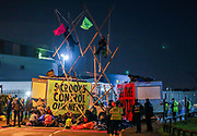 Two Extinction Rebellion activists stand on a bamboo lock-on to maintain the blockade throughout the night aiming to prevent the Sun, Times, Telegraph and Mail newspapers from reaching newsstands on Saturday, Sept 5, 2020. The action took place in Broxbourne in Hertfordshire (in the picture) and Knowsley in Liverpool. Extinction Rebellion (XR) said about 80 activists were involved. Environmental nonviolent activists group Extinction Rebellion enters its 5th day of continuous ten days protests to disrupt political institutions throughout peaceful actions swarming central London into a standoff, demanding that central government obeys and delivers Climate Emergency bill. (VXP Photo/ Vudi Xhymshiti)