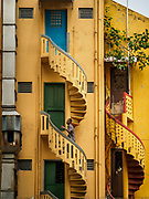 13 DECEMBER 2018 - SINGAPORE: A man goes up the stairs to his apartment in a shophouse building in the Geylang neighborhood. The original shophouses of Singapore are disappearing. Some are being torn down to make way for high rise developments, others are being gentrified into touristy shops and restaurants. The Geylang area of Singapore, between the Central Business District and Changi Airport, was originally coconut plantations and Malay villages. During Singapore's boom the coconut plantations and other farms were pushed out and now the area is a working class community of Malay, Indian and Chinese people. In the 2000s, developers started gentrifying Geylang and new housing estate developments were built.     PHOTO BY JACK KURTZ