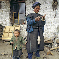 CHINA, TIBET, Tsangpo Gorge. Young mother spins wool outside family's house in Kykar village.
