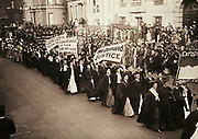Women in academic dress marching in a suffrage parade in New York City, 1910.<br />