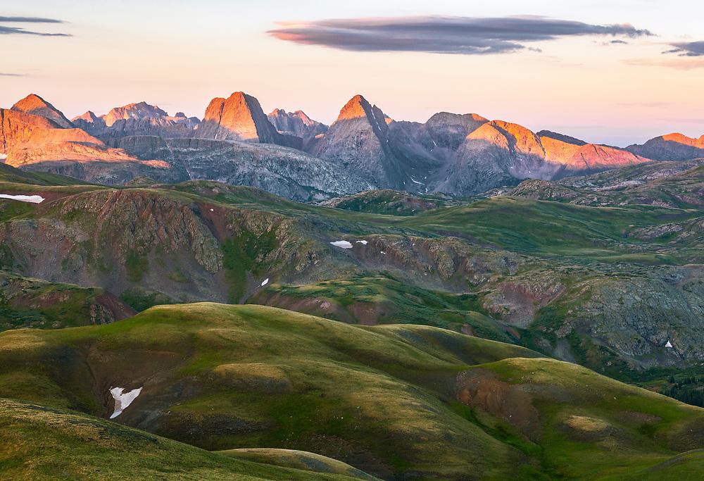 The rugged Grenadier Range rises above the rolling green tundra, Weminuche Wilderness