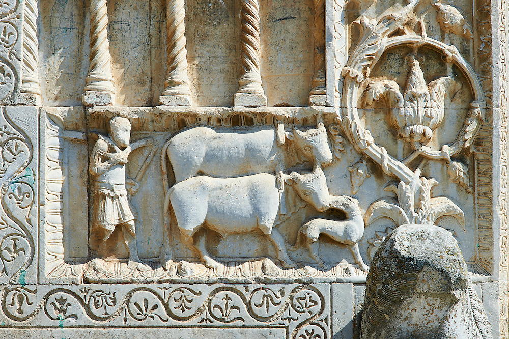 Sculpture of a man with two cows on the 12th century Romanesque facade of the Chiesa di San Pietro extra moenia (St Peters), Spoletto, Italy .<br /> <br /> Visit our ROMANESQUE SCULPTURE PHOTO COLLECTION for more   photos  to download or buy as prints https://funkystock.photoshelter.com/gallery/Romanesque-Statue-Sculptures-Pictures-Images/G0000ezFHYeF_xRI/C0000YpKXiAHnG2k<br /> If you prefer to buy from our ALAMY PHOTO LIBRARY  Collection visit : https://www.alamy.com/portfolio/paul-williams-funkystock/pietro-extra-moenia-spoleto.html .<br /> <br /> Visit our MEDIEVAL PHOTO COLLECTIONS for more   photos  to download or buy as prints https://funkystock.photoshelter.com/gallery-collection/Medieval-Middle-Ages-Historic-Places-Arcaeological-Sites-Pictures-Images-of/C0000B5ZA54_WD0s