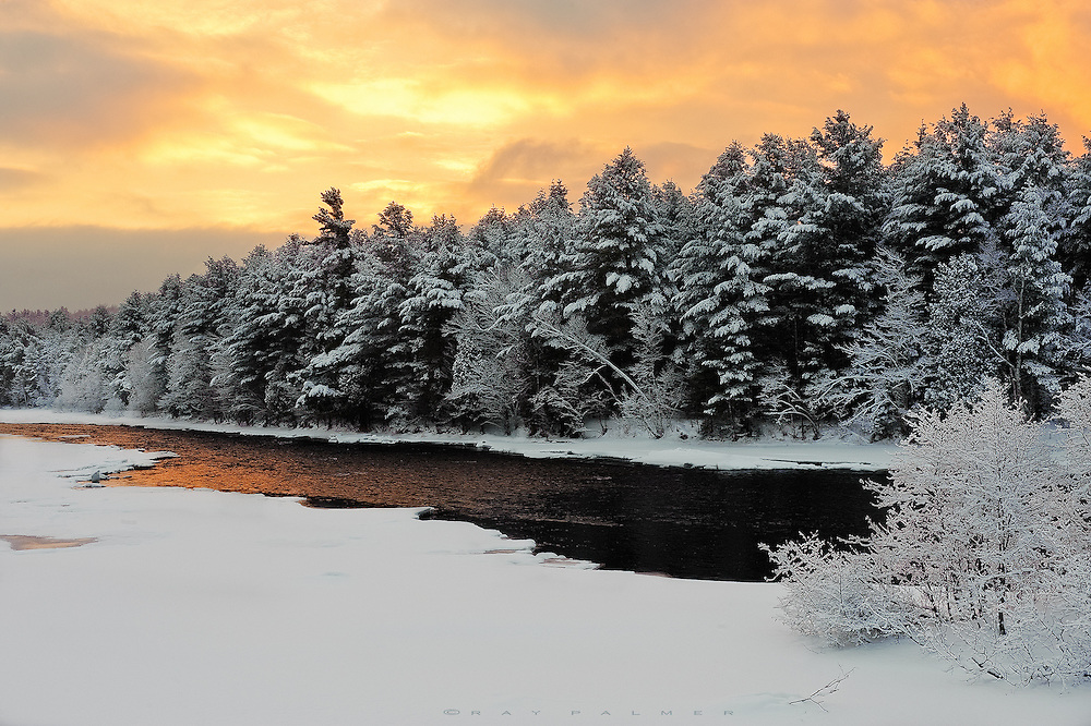 Winter, Saranac River, Adirondacks, NY.  Overnight, a storm blew through, sifting a fresh coat of white on the world.  I came in at the end, when the snow had stopped, and the sky still roiled with heavy clouds, lit from behind as the sun rose.  It would be a battle, to see if the cloud cover held or would be broken by daylight.   The open water on the river glowed as if it were the source of light instead of the dark water it really was.  I waited to see who would win.