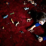 Autistic child Rowan, 5, plays with animals at a Mongolian hotel. .Rowan's parents believe horses and shamans can unlock their sonís autistic mind. This is their journey of discovery across Mongolia on horseback. .The story is published by the Sunday Times and accompany text by Tim Rayment.
