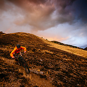 Malachi Artise riding through a recent wildfire burn as a summer thunderstorm clears at sunset.