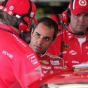 NASCAR Sprint Cup driver Juan Pablo Montoya (center) speaks with a team member in the garage area, during a NASCAR Daytona 500 practice session at Daytona International Speedway on Wednesday, February 20, 2013 in Daytona Beach, Florida.  (AP Photo/Alex Menendez)