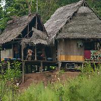 A family eats in its hut in San Juan de Yanayacu village by the Yanayacu River in Peru's Amazon Jungle.