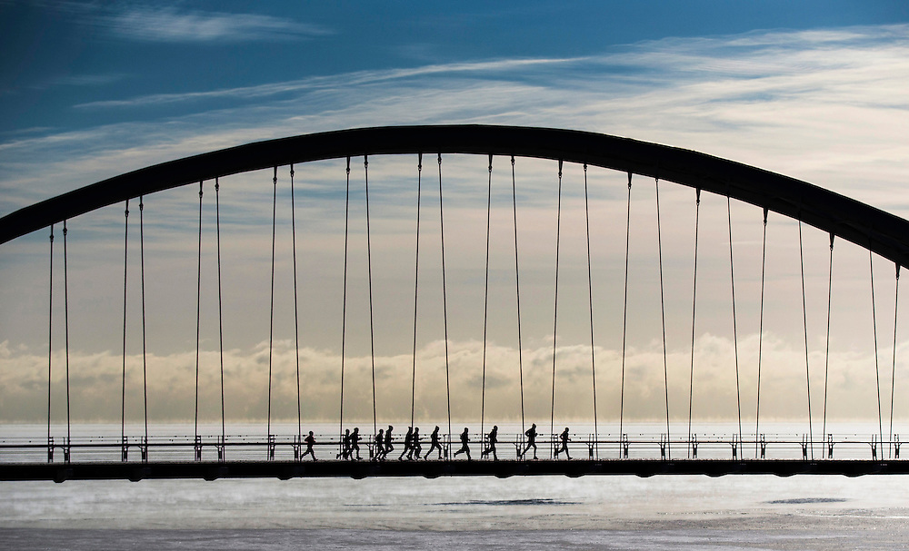 """A group of joggers run across the Humber Bay Arch Bridge during extreme cold temperatures in Toronto, February 16, 2015.  Toronto experienced some of the coldest weather of the year reaching -25C (-13F) on Sunday, as Environment Canada lifted its """"extreme cold weather alert"""" Monday when temperatures warmed to -13C (8.6F),    according to local reports.   REUTERS/Mark Blinch (CANADA)"""