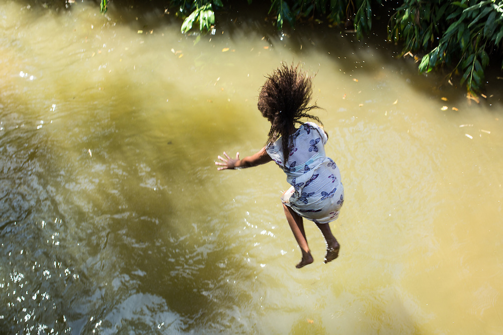 A girl jumps into the Pedro Cubas river.<br /> <br /> Pedro Cubas is one of many quilombos that is taking part in the Movement of People Affected by Dams (Movimento dos Atingidos por Barragens, MAB) who are in active resistance against new dams in the region. The quilombo sits on the small river also called Pedro Cubas.<br /> <br /> Quilombos are remote hinterland settlements in Brazil set up by escaped slaves of African origin. Though most of them were destroyed by slave owners and the Brazilian state, today there are around 5,000 recognised quilombos in Brazil. Slavery was legal in Brazil for four centuries and some five million slaves were brought to Brazil, most of them from the Angola area. Today the largest population of people of African descent in the world, with the exception of Nigeria, is Brazil.<br /> <br /> When the owner of the Caiacanga farm died in the 18th century, the slaves he owned disappeared and hid in the forest, one of them was Gregorio Marinho who established the Pedro Cubas quilombo with other escaped slaves from farms and the gold mines in the region.<br /> <br /> The Pedro Cubas community has 3,800 hectares and around 60 families and 230 people, most of them under 15.<br /> <br /> The community farms collectively to produce cassava, yam, sweet potato, corn, beans, banana and sugar cane. <br /> <br /> Like many quilombos, it is remote. For centuries, rivers were the main means of transport, so the closer a quilombo community was to a large river, the greater the likelihood of being discovered and destroyed. The 5000 quilombos that survived are mainly in hinterlands and access can be difficult. To reach Pedro Cubas the river to cross on the only way in is using a ferry that is operated without an engine, using only the flow of the river.<br /> <br /> The lands of Pedro Cubas were partially titled in 2003 by the government of the State of São Paulo. But, despite the decree, non-quilombola occupants remain in the area.